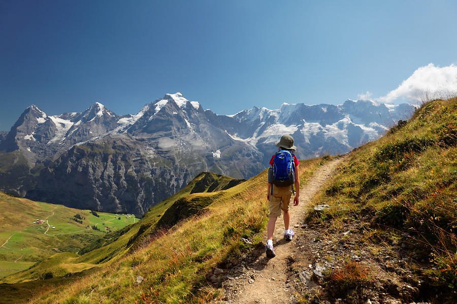 Girl hiking trail on Wasenegg ridge on Schilthorn mountain, villages of Schiltalp and Gimmeln below, Eiger, Mönch and Jungfrau in background, Switzerland