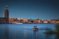 Båtfärd på Riddarfjärden en sen kväll i Stockholm med Stadshuset, Rosenbad och Riksdagshuset.