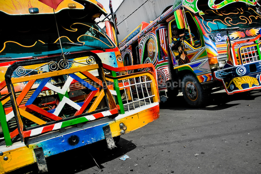 Tap-tap buses pass through the downtown of Port-au-Prince, Haiti, 25 July 2008. Tap-tap vehicles serve as public transportation in Haiti. They are private, operate over fixed routes, departing only when full. Tap-taps are decorated with bright and shiny colors and with a lot of fancy designed elements. There are scenes from the Bible, Christian slogans, TV stars or famous football players often painted on a tap-tap body. Tap-tap name comes from sound of taps on the metal bus body signifying a passenger's request to be dropped off.
