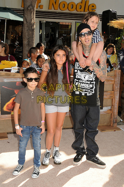 guests, Travis Barker and Alabama.The L.A. Premiere of 'Puss in Boots' held at The Regency Village Theatre in Westwood, California, USA..October 23rd, 2011.full length black sleeveless top tattoos hat sunglasses shades sitting on shoulders father dad daughter family stripe top jeans denim.CAP/ADM/BP.©Byron Purvis/AdMedia/Capital Pictures.