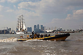 London, UK. 9 September 2014. A Thames Rip Experience boat in front of tall ships and Canary Wharf with the Millennium Dome. The Tall Ships that have taken part in the Royal Greenwich Tall Ships Festival 2014 leave Greenwich in a Parade of Sail down the River Thames.