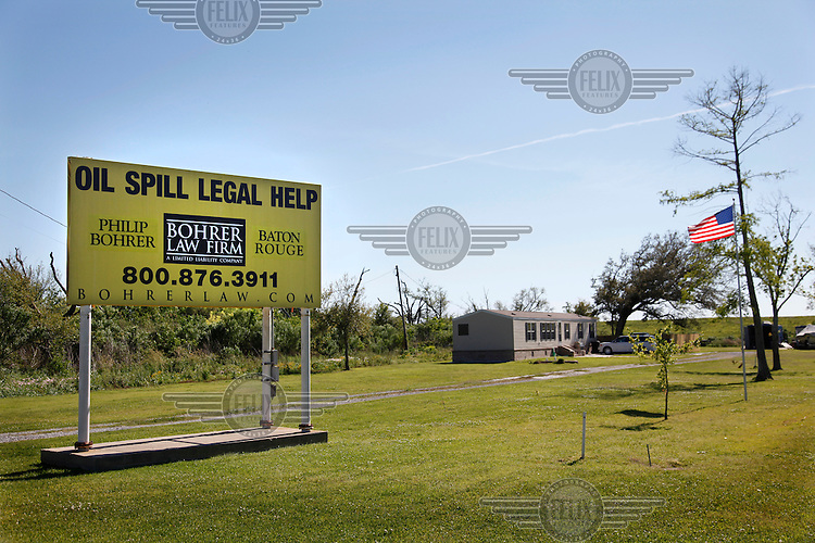 A billboard sign offering legal services for people claiming damages from BP following the Deep Water Horizon oil spill,  that began on 20 April 2010, on a front lawn near Venice, Louisiana.