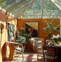 Sun pours through the glass roof of this terracotta coloured garden room which is furnished with a selection of wicker chairs