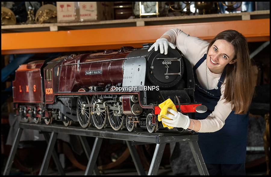 BNPS.co.uk (01202 558833)<br /> Pic: PhilYeomans/BNPS<br /> <br /> Kerry Mitchell from Dreweatts with the stunning locomotive.<br /> <br /> Track Record?- 'Best railway model ever built' is getting train buffs all steamed up.<br /> <br /> A stunning model train described as 'one of the best ever built' could break a world record when it goes under the hammer.<br /> <br /> The maroon coloured scaled down version of the 'Duchess of Buccleuch' is one of just two of that model made by legendary train builder Harry Powell.<br /> <br /> Its sister model sold for a world record £183,000 seven years ago - and it is hoped this one could top that sum.<br /> <br /> The 10ft model took Powell, who is regarded as the 'Rembrandt of model train making', 10 years and 18,000 hours to build.