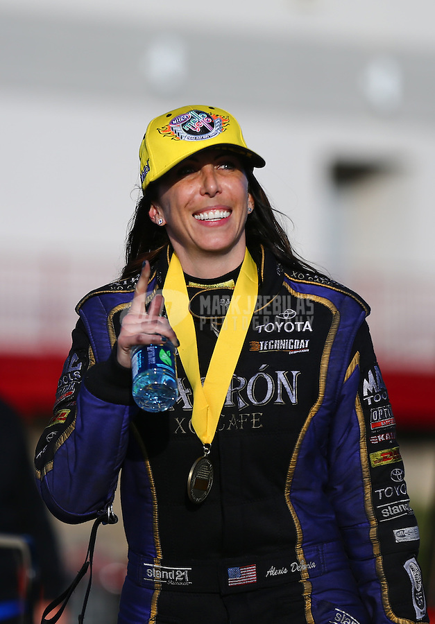 Mar 30, 2014; Las Vegas, NV, USA; NHRA funny car driver Alexis DeJoria celebrates after winning the Summitracing.com Nationals at The Strip at Las Vegas Motor Speedway. Mandatory Credit: Mark J. Rebilas-