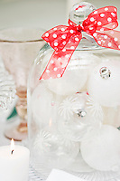 One of the table decorations is a glass cloche filled with transparent Christmas baubles