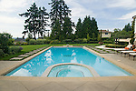 Two lots were combined to make room for this fantastic yard and poolside outdoor living area in this suburban community east of Seattle, including geometric patterned paving to set the pool apart and a long swimming pool with a built in tiled spa.