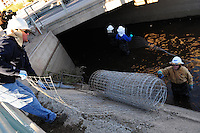 Scottsdale, Arizona (January 12, 2013) - As part of a seven-year plan to dry up all portions of its 131-mile canal system, Salt River Project (SRP), relocated the White Amur fish they used as an environmentally friendly and cost effective alternative to herbicides and heavy machinery for vegetation control. In this image, SRP employees get ready for the fish herding process by bringing wire fence into the shallow waters of the canal to corral the fish into a collection area. Photo by Eduardo Barraza © 2013
