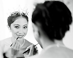 Erina Takahashi looks into the mirror while applying makeup.