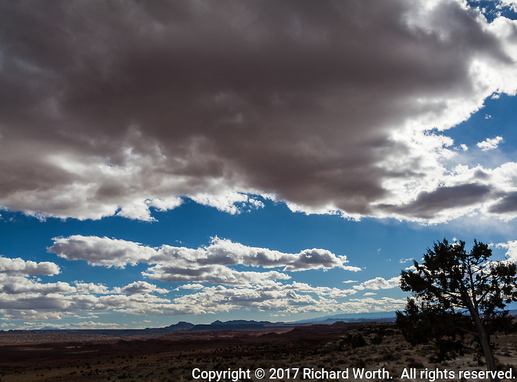 Clouds float over the Utah desert on a late fall afternoon, with a faint tinge of the reflected red desert below.