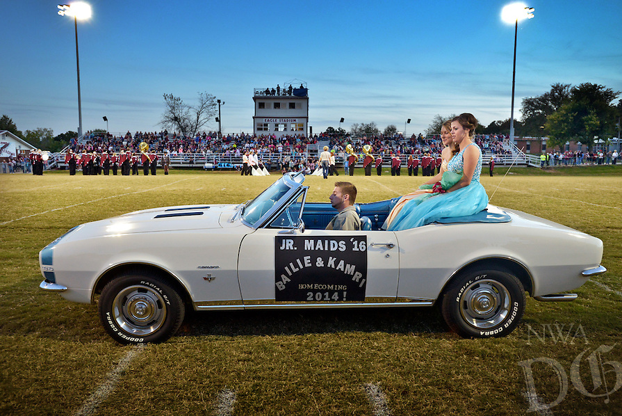 STAFF PHOTO BEN GOFF  @NWABenGoff -- 10/17/14 Kamri Thomas, 16, and fellow junior maid Bailie Ingraham, 17, fore, ride into Huntsville's Eagle Stadium in a convertible during pre-game homecoming festivities before the football game between Lincoln and Huntsville on Friday October 17, 2014.