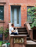 Emulating the original black and white photograph of the property, owner/architect Jeff Sherman and his dog on the steps following its restoration