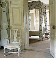 View through open double doors into the master bedroom with its canopied four-poster bed