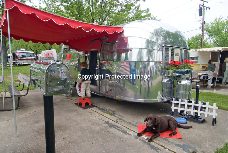 Brown dog and kid hanging out in front of a siler 1953 Airstream Flying Cloud vintage travel trailer.