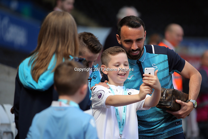 SWANSEA, WALES - APRIL 22: Leon Britton of Swansea City has his picture taken by young fans prior to the Premier League match between Swansea City and Stoke City at The Liberty Stadium on April 22, 2017 in Swansea, Wales. (Photo by Athena Pictures/Getty Images)