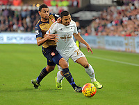 (L-R) Francis Coquelin of Arsenal challenges Jefferson Montero of Swansea during the Barclays Premier League match between Swansea City and Arsenal at the Liberty Stadium, Swansea on October 31st 2015