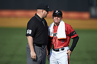 Louisville Cardinals head coach Dan McDonnell (right) listens as first base umpire Wilson Raynor explains a call during the game against the Wake Forest Demon Deacons at David F. Couch Ballpark on March 17, 2018 in  Winston-Salem, North Carolina.  The Cardinals defeated the Demon Deacons 11-6.  (Brian Westerholt/Four Seam Images)