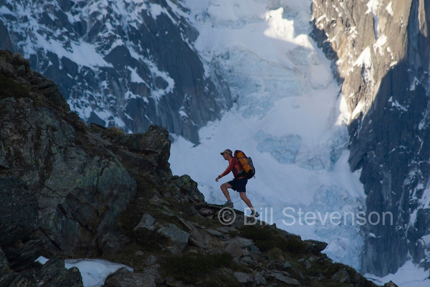 A photo of a man hiking by a glacier and granite spires near Chamonix in the French Alps