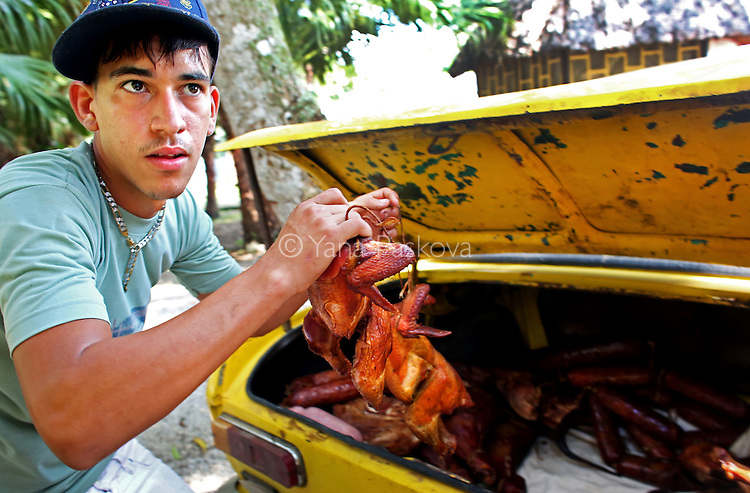 A man prepares whole grilled chicken for sale transported in the trunk of his Moskvitch, an automobile made by Russia from 1946 to 2002, before a cock-fighting event at a sports arena on April 18, 2015 in Managua, Cuba. Cock-fighting in Cuba is in the gray area of legal - state-run events such as this (non-private) functions are permitted, but not monetary betting. This is in part due to lingering bitterness over the control U.S. mafia used to exercise over casinos and prostitution in pre-revolutionary Cuba, the income from which allowed crime lords a certain level of interference in the country's political matters. <br /> <br /> Cuba, a place of much recent conversation, is a country whose politics and way of life parallel much of my childhood in Bulgaria. This is 2015's continuation to my project on democracy + communism, started last year on the 25th anniversary of the fall of the Berlin Wall - the event that gave opportunity to Eastern Europeans like me to immigrate to the Western world. These are the ways in which Cuba has transported me to pre- and post-1989 Bulgaria. This project is supported by a grant from The Pulitzer Center on Crisis Reporting.