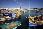 Colourful fishing boat Luzzu docking in the port of Marsaxlokk. Malta