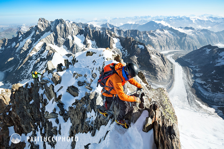 A climber nearing the summit of the Finsteraarhorn with big views of the Berner Oberland's alpine landscape below. The Finsteraarhorn is the Berner Oberland's tallest mountain.