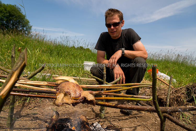 6/22/2015 &mdash; Everett, WA, USA<br /> <br /> Steven Rinella, an avid outdoorsman and hunter, cooks both wild duck and domesticated chicken over an open wood fire in Everett, WASH. <br /> <br /> <br /> Both birds were skewered with branches cut from nearby Alder trees and hung over the fire using more Alder branches.<br /> <br /> <br /> <br /> Photograph by Stuart Isett<br /> &copy;2015 Stuart Isett. All rights reserved.