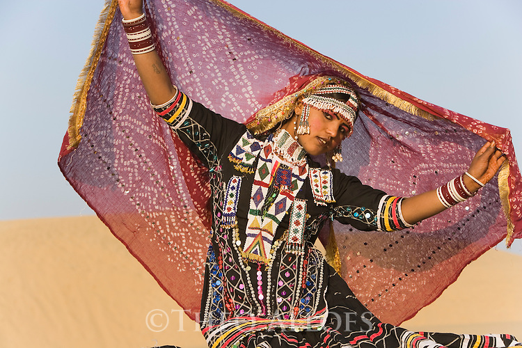 Rajasthani dancer in traditional costume performing on sand dunes in the Thar Desert;  Rajasthan, India ---Model Released