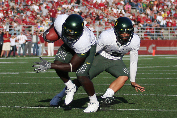 Oregon running back, LeGarrette Blount (#9), gets the handoff from Duck quarterback, Jeremiah Masoli (#2), during the Ducks Pac-10 conference game against the Washington State Cougars at Martin Stadium in Pullman, Washington, on September 27, 2008.