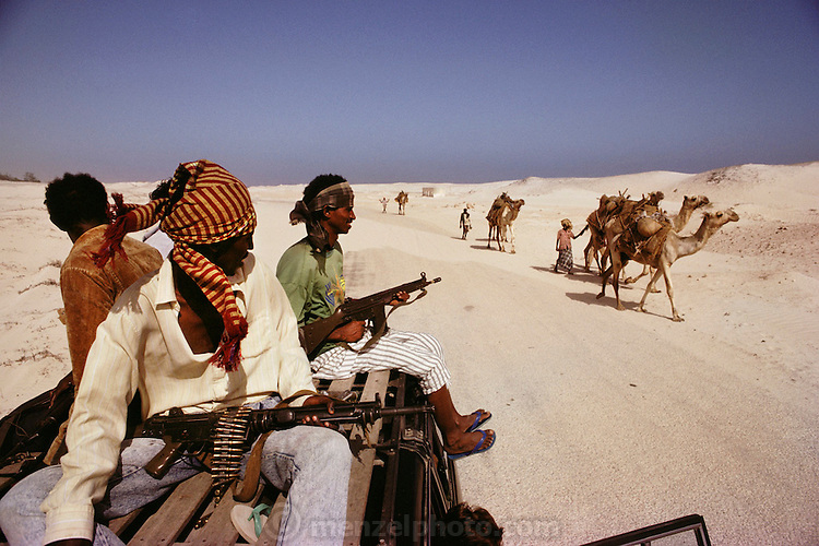 Foreign aid workers on their day off on their way to the beach with armed guards pass camels in Mogadishu, the war torn capital of Somalia. March 1992.