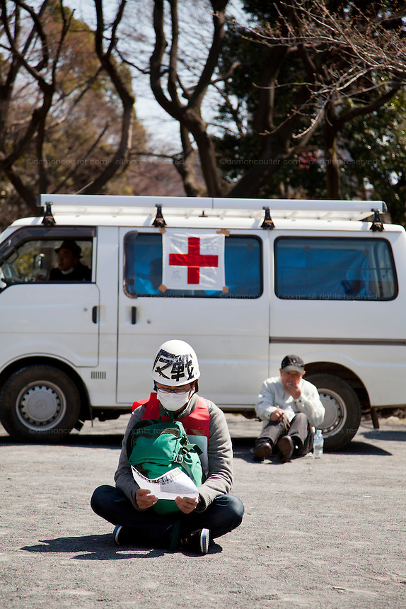 A union activist sits and reads pamphlets in front of a first aid van at a left wing demonstration against the exploitation of farmers during the construction of Narita Airport. Shiba Park, Tokyo, Japan. Sunday March 23rd 2014 The main organiser of the protest was The Farmers' league Against Narita Airport. Around 1,000 activists from this league and other unions took part.