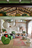 A rustic style living room with a pitched beamed roof and a wood floor. The room is furnished with two moulded green chairs, a dining table and three large paper globe lights hang from the ceiling.