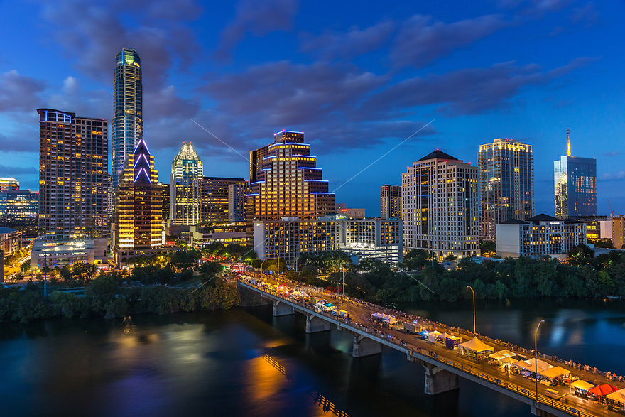 This colorful image featuring the Austin Skyline in all it's glory during the annual Austin Bat Festival is voted Austin's most popular and best event. The festival features 20,000 bat enthusiast coming to celebrate the flight of 1.5 million Mexican free-tailed bats emerging from under the Congress Avenue Bridge at dusk, three stages with live music, more than 75 arts & crafts vendors, delicious food and drinks, fun children's activities, a bat costume contest and other bat activities.