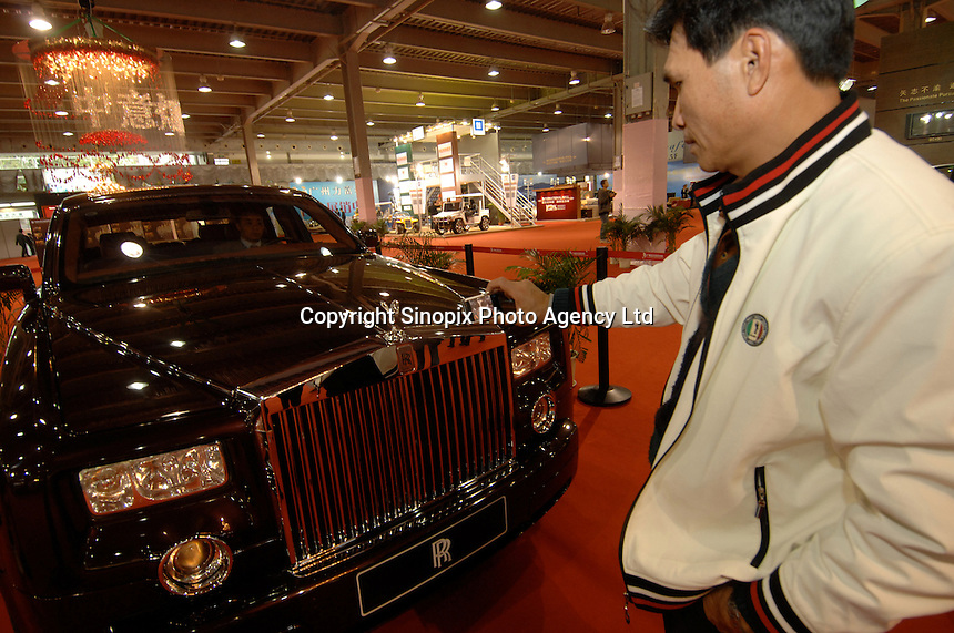 A man takes photo of Rolls Royce Phantom at the Guangzhou luxury goods fair in China. .16 Dec 2006