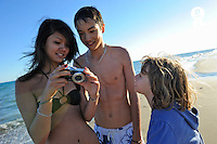 Three children taking pictures together on beach (Licence this image exclusively with Getty: http://www.gettyimages.com/detail/105765533 )