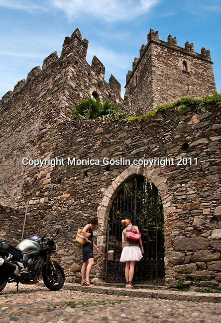 Two girls look up at a castle in Rezzonico, a town on Lake Como, Italy