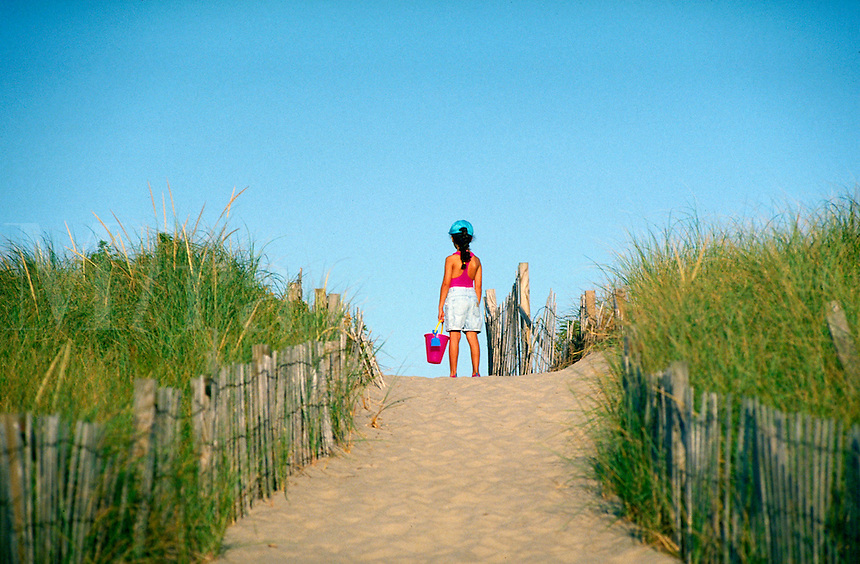 Girl with sand bucket standing at beach entrance, Cape Cod National Seashore, Cape Cod, MA