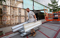 NWA Democrat-Gazette/DAVID GOTTSCHALK Leslie Alley, with Structure Framing, carries Tuesday, July 3, 2018, metal facade removed from the west side of the former First National Bank building on the square in Fayetteville. Work on the removal of the facade, consisting of steel, aluminum and granite, will continue through the week in preparation for restoration of the original exterior.