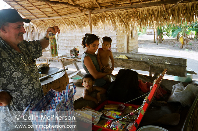 A mother and her children looking at toys brought to their village in a protected reserve by a travelling salesman. The Floresta Nacional do Tapajos (FLONA), a 6500 km2 protected reserve, was home to several small communities which lived on the banks of the Rio Tapajos river. The communities did not have electricity or running water and access to the villages was by unpaved dirt roads from Santarem and Highway BR163.