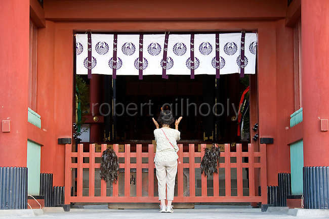 A woman prays in front of the inner sanctuary -- in front of which seaweed has been draped -- during the annual Reitaisai Grand Festival at Tsurugaoka Hachimangu Shrine in Kamakura, Japan on  14 Sept. 2012.  Sept 14 marks the first day of the 3-day Reitaisai festival, which starts early in the morning when shrine priests and officials perform a purification ritual in the ocean during a rite known as hamaorisai and limaxes with a display of yabusame horseback archery. Photographer: Robert Gilhooly