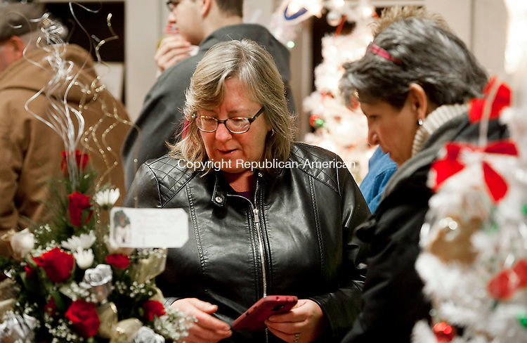 THOMASTON, CT--- -112815JS028-Pat Daigle and Diane Xander, both of Plymouth, look over the trees on display and open to bids, at the Festival of Trees in the Crescent Gallery during the annual Light Up Thomaston event Saturday in downtown Thomaston. <br /> Jim Shannon Republican-American