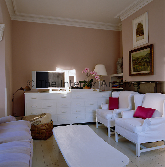A wooden African bed has been painted white to match the other furniture and is used as a coffee table in the family room