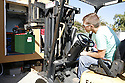 A Solar Decathlon team member drives a forklift to install one of many massive storage batteries in their solar home to capture energy from the solar panels.