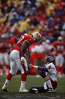 SAN FRANCISCO, CA:  Bryant Young of the San Francisco 49ers stands over Chicago Bears quarterback Steve Walsh during the NFC playoff game at Candlestick Park in San Francisco, California on January 7, 1995. (Photo by Brad Mangin)