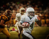 Mt. Carmel running back Jimmy Mickens breaks away from Loyola defenders for a touchdown in the second quarter Saturday