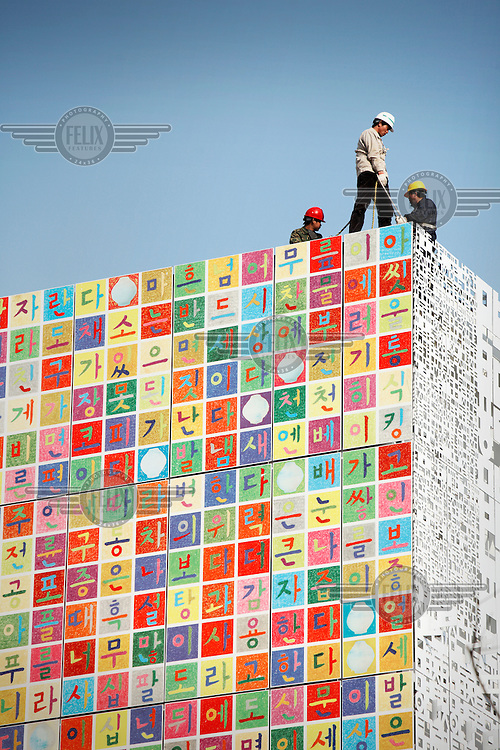 Workers standing on top of the Republic of Korea (South Korea) Pavilion at the 2010 World Expo site.