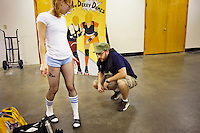 Pussy Venom's boyfriend Kevin checks out her fishnet stockings before a roller derby bout in Wilmington, Massachusetts. Roller derby is an American contact sport, popular with young women, which combines both athleticism and a satirical punk third-wave feminism aesthetic.