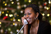 First Lady Michelle Obama reacts while talking on the phone to children across the country as part of the annual NORAD Tracks Santa program. Mrs. Obama answered the phone calls from Kailua, Hawaii, Christmas Eve, Dec. 24, 2012..Mandatory Credit: Pete Souza - White House via CNP