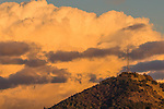 Butte Mountain with communications tower with late autumn passing storm cloud build at sundown.