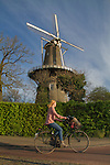 Woman cycling and windmill, Leiden, Netherlands.