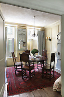 A wrought iron chandelier hangs above a period wooden dining table and chairs in a painted panelled dining room. An open door gives a view to a modern kitchen beyond.
